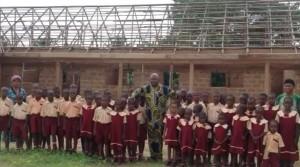 Foto: Pfarrer Charlie mit seinen Schulkindern vor dem Rohbau der neuen Schule, Umulokpa, Nigeria, Juni 2013