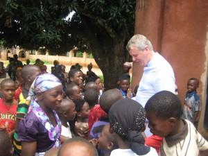 """Foto: Pastor Bernd de Baey mit Kindern vor der Sakristei von """"Holy-Cross, Nigeria, Sommer 2012"""